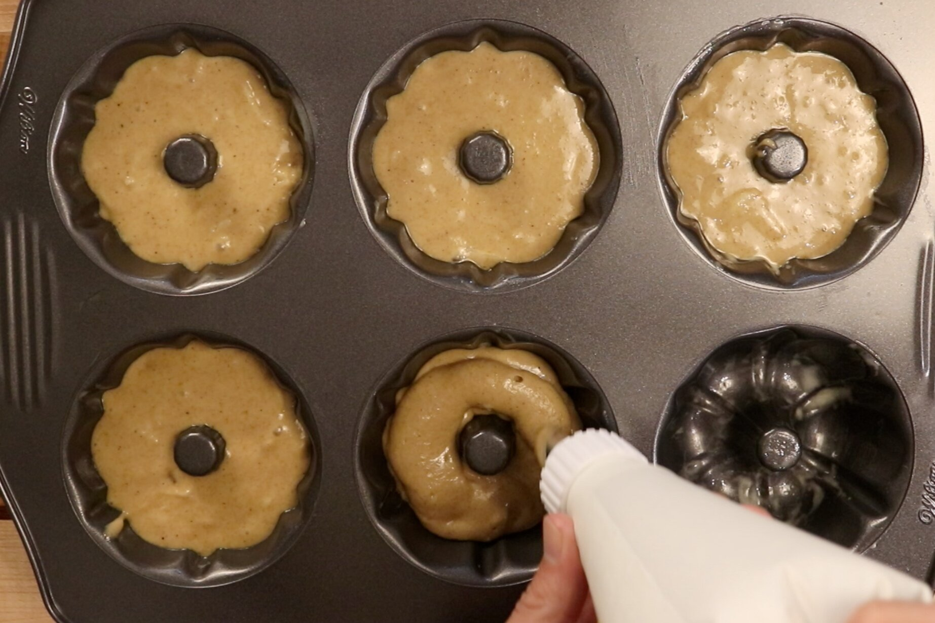 7. Spoon or pipe your batter evenly between bundt cups filling 1/2 of the way full. -