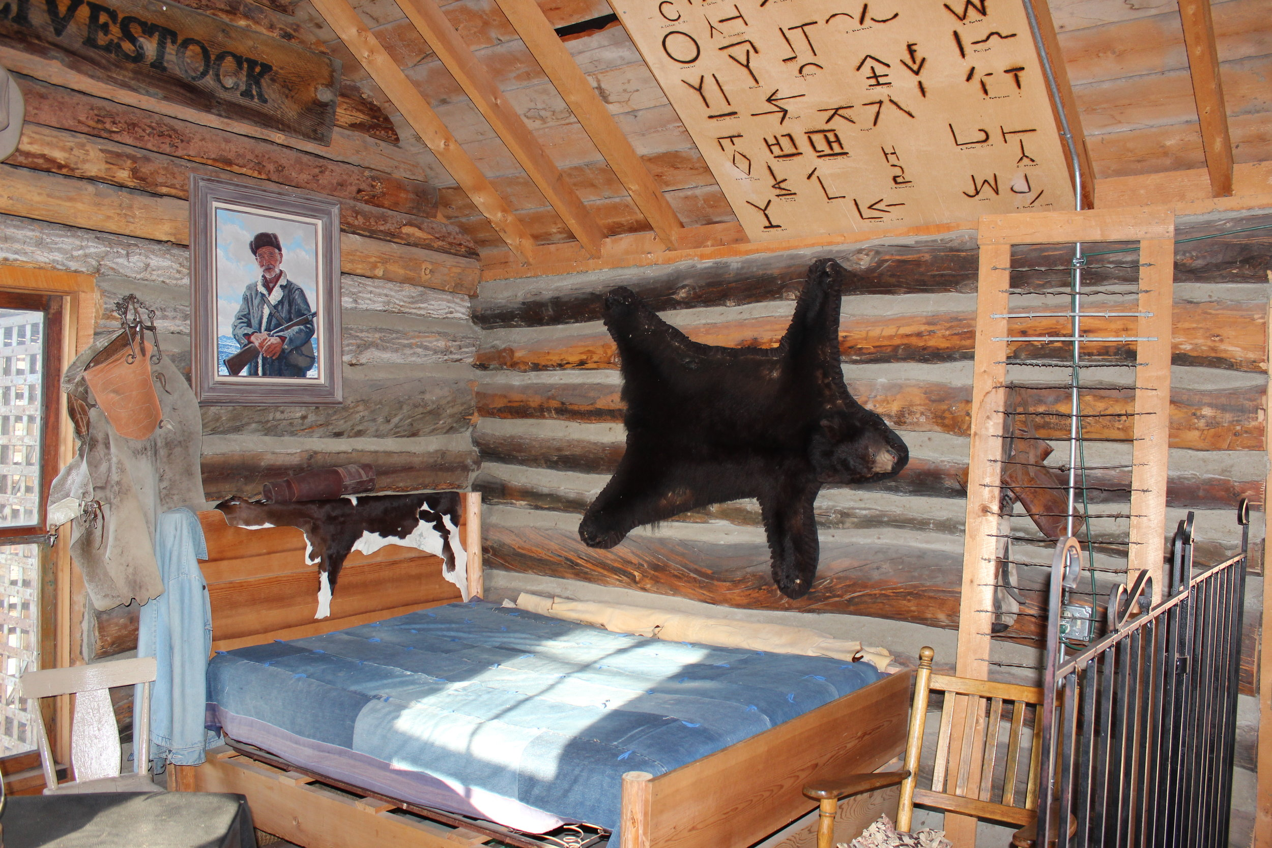 Brands from local families hang above the bed in the cowboy camp.