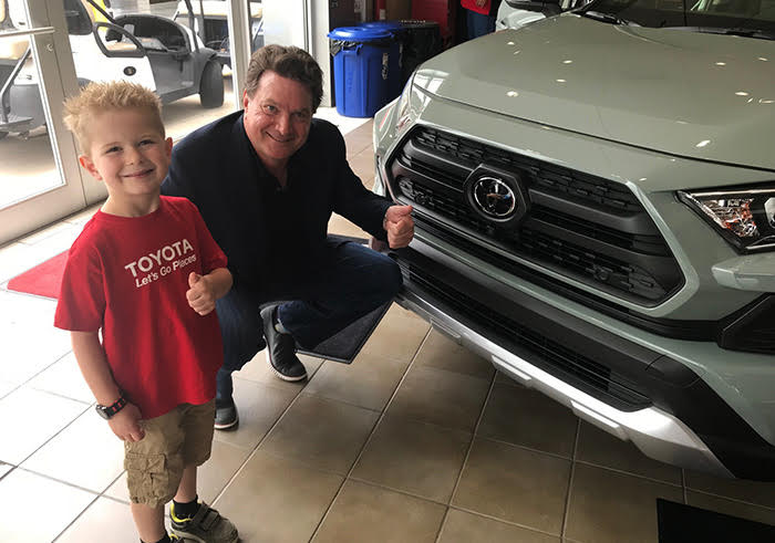 Thumbs Up –    Ed Laukes, group vice president of Toyota Division marketing, helps Holden Monson celebrate his sixth birthday at Steve Landers Toyota of Northwest Arkansas.