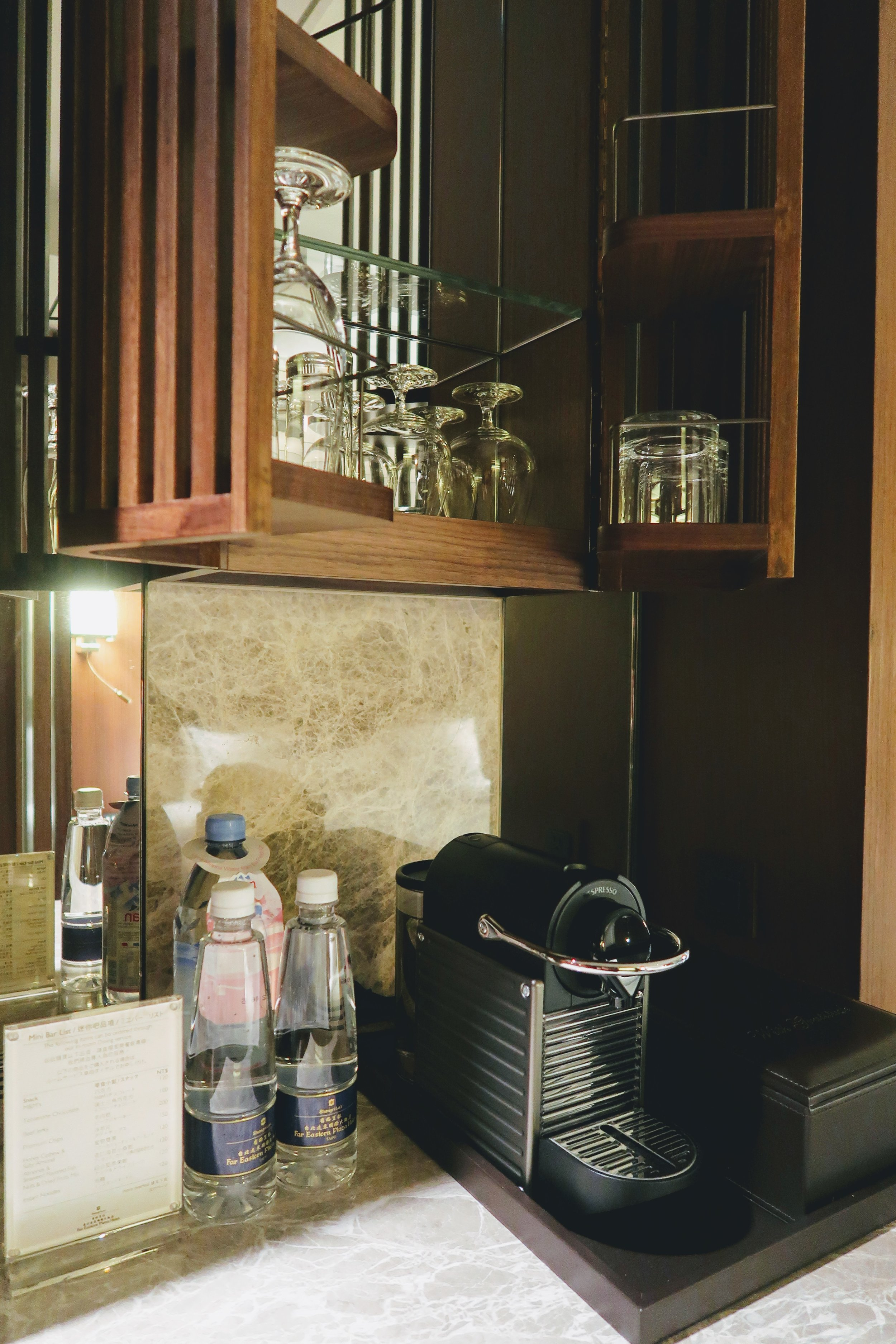 Nespresso coffee machine, free bottles of water and an impressive top cabinet containing the glasswares.