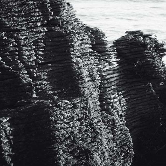 "We spent an almost full day making our way back up north from Wanaka. We headed to the famous ""Pancake Rocks"" on the northwest coast near Punakaiki. The Pancake Rocks are a heavily eroded limestone area where the sea bursts through several vertical blowholes during high tides. Overall, scientist are a bit baffled about exactly how these formations came about. It seems like they were formed by alternating settings of ocean sediment but under high pressure. However, just what in nature that would cause a highly pressurized environment is the befuddling part. . . Has anyone else came across something similar anywhere else? . . #pancakerocks #newzealand #purenewzealand #layers #blackandwhite #sunsetvibes #clouds #blowholes #sciencequestions #geology #naturalwonders #naturephotography #landscapephotography #oceania #360waves"