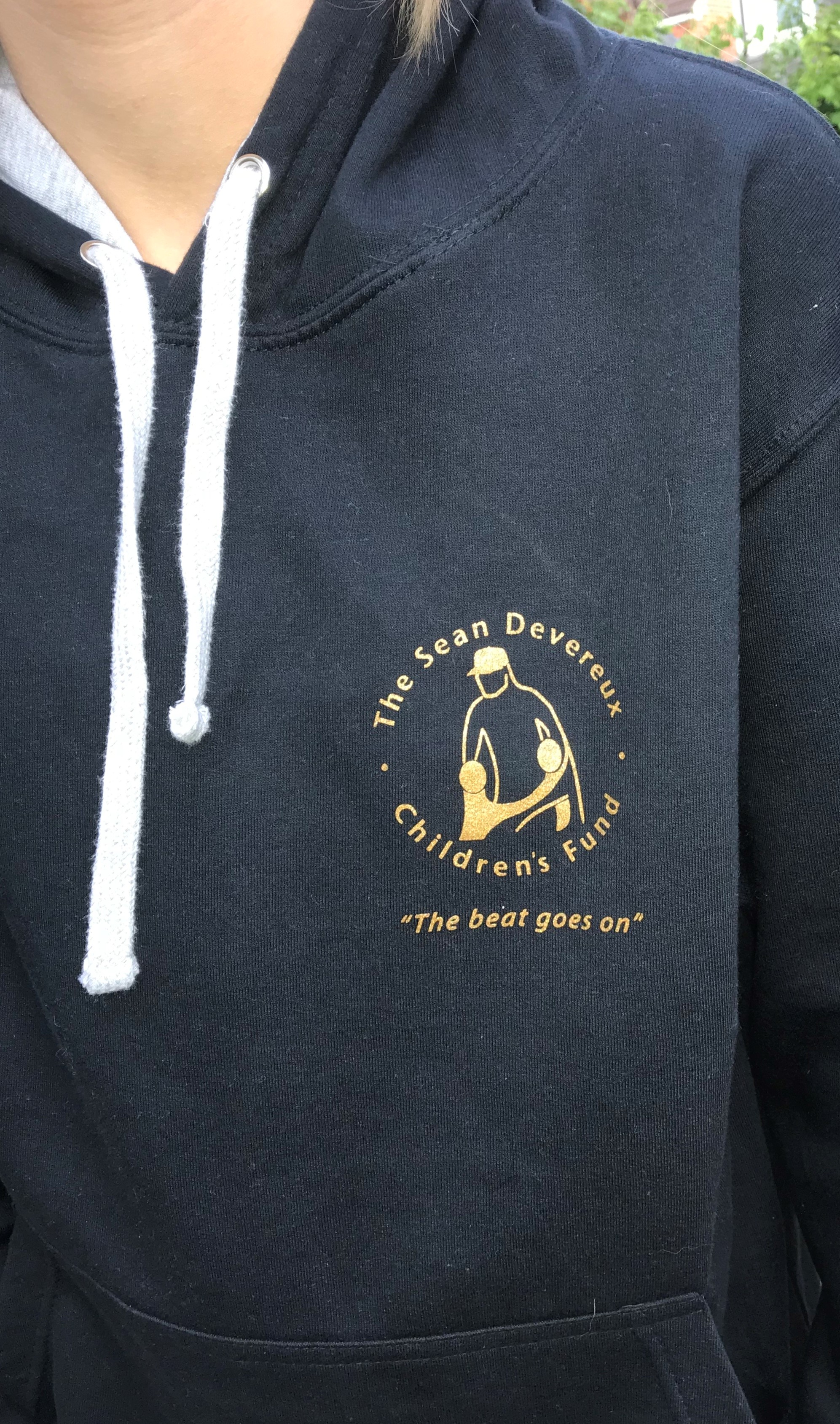 The hoodies, which are unisex, are dark navy with a heather grey contrast hood and come in sizes from XS-XL. The logo is in gold on the front and features the inspirational words,