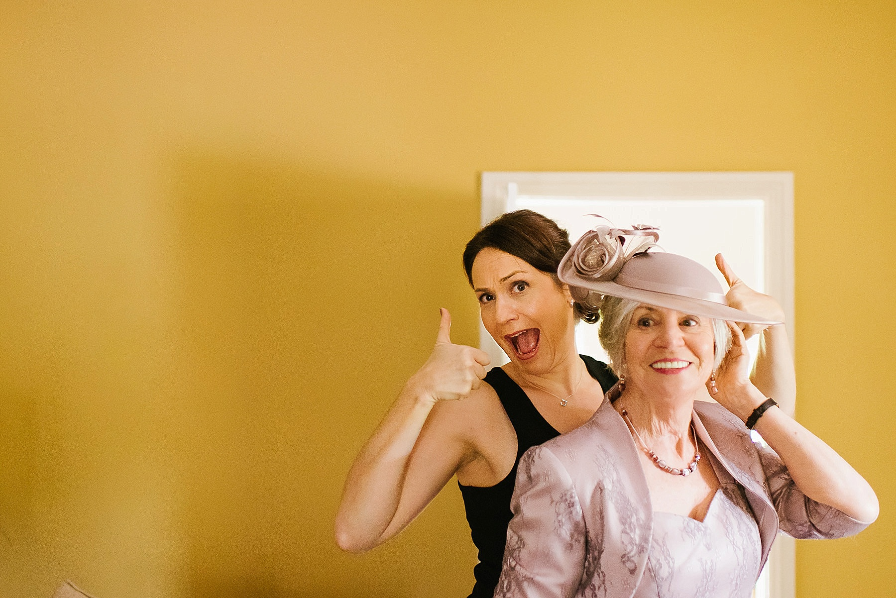 Bride giving thumbs up behind her mum