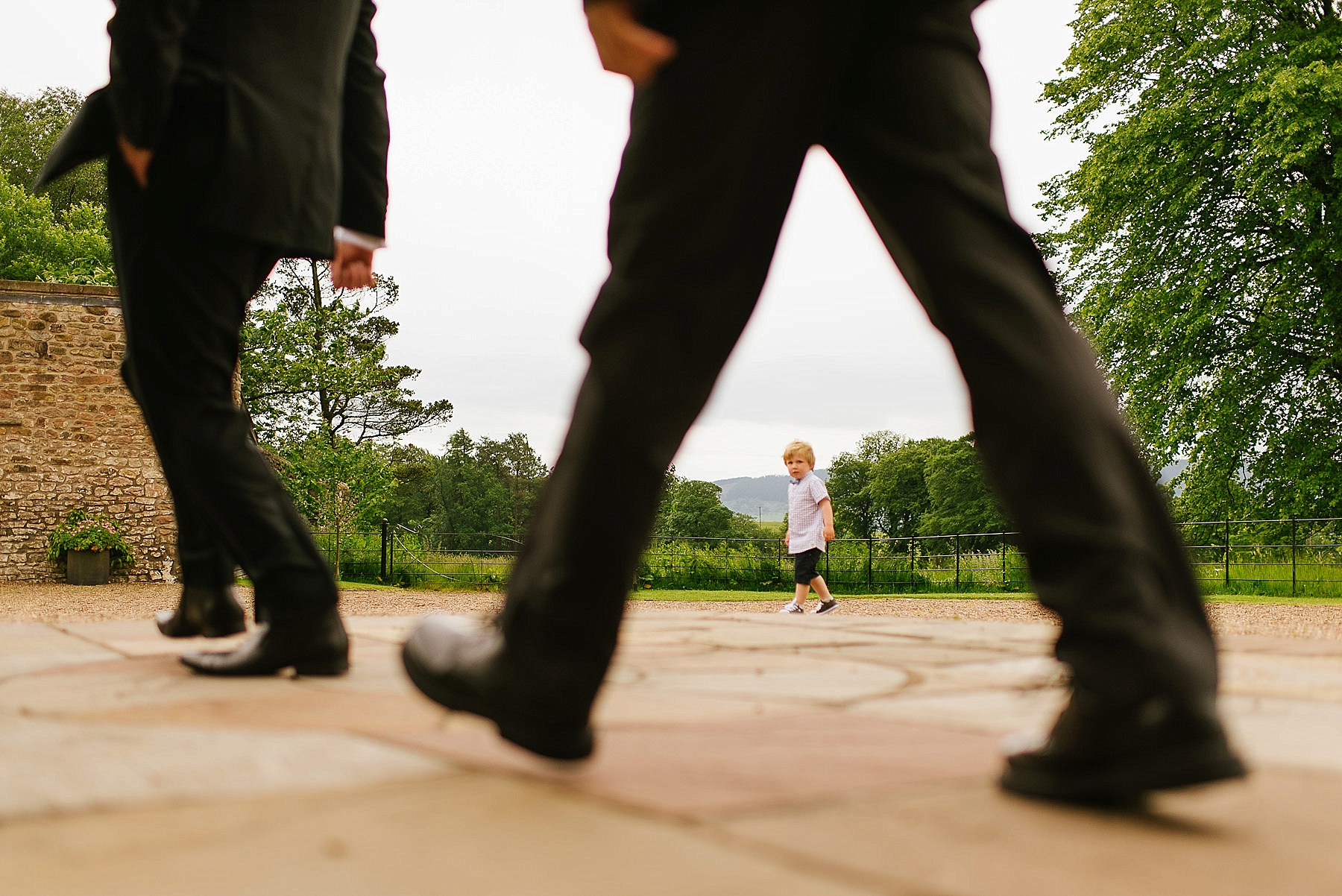 legs walking and in the background a child looks at the camera