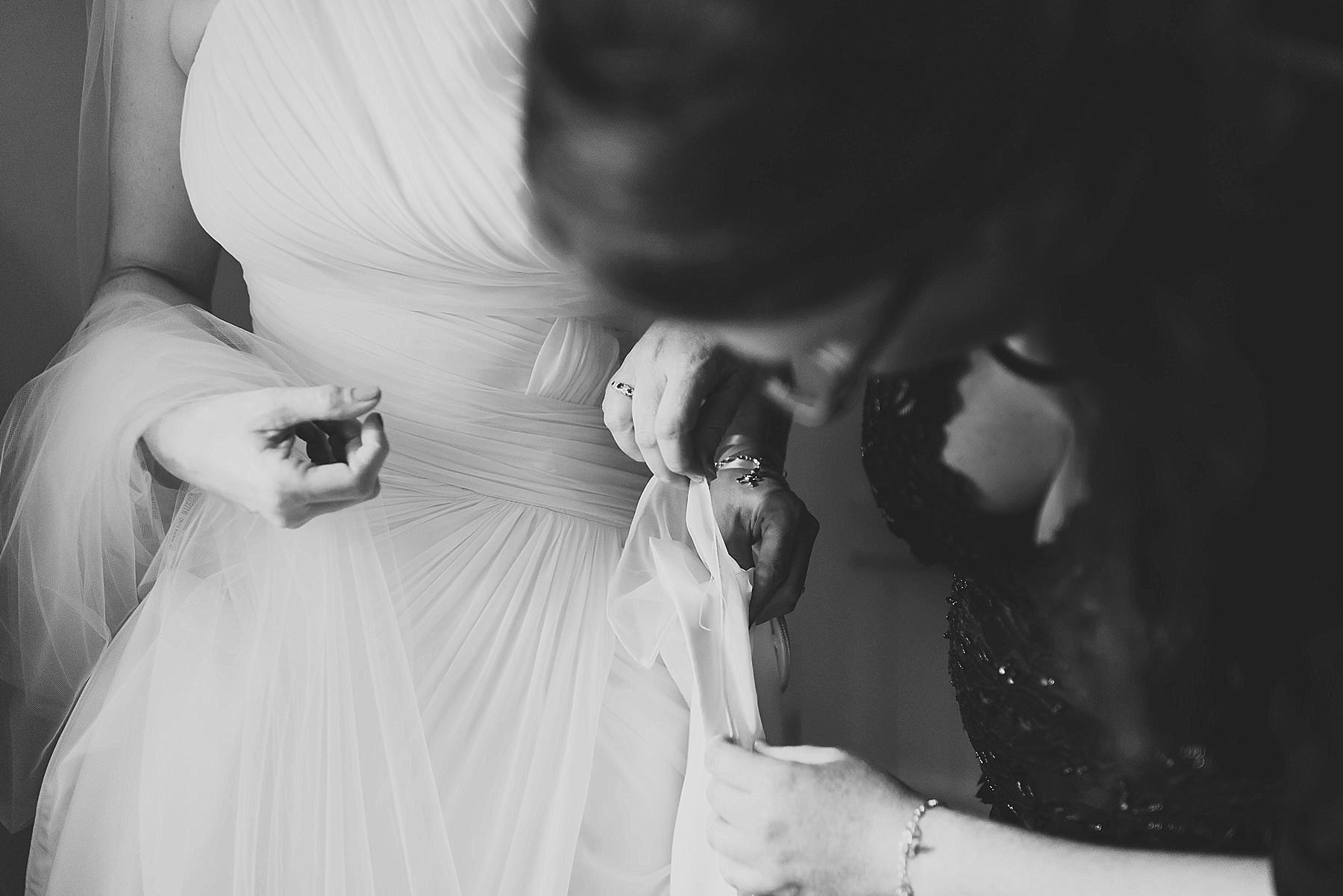 bridesmaid fixing the wedding dress