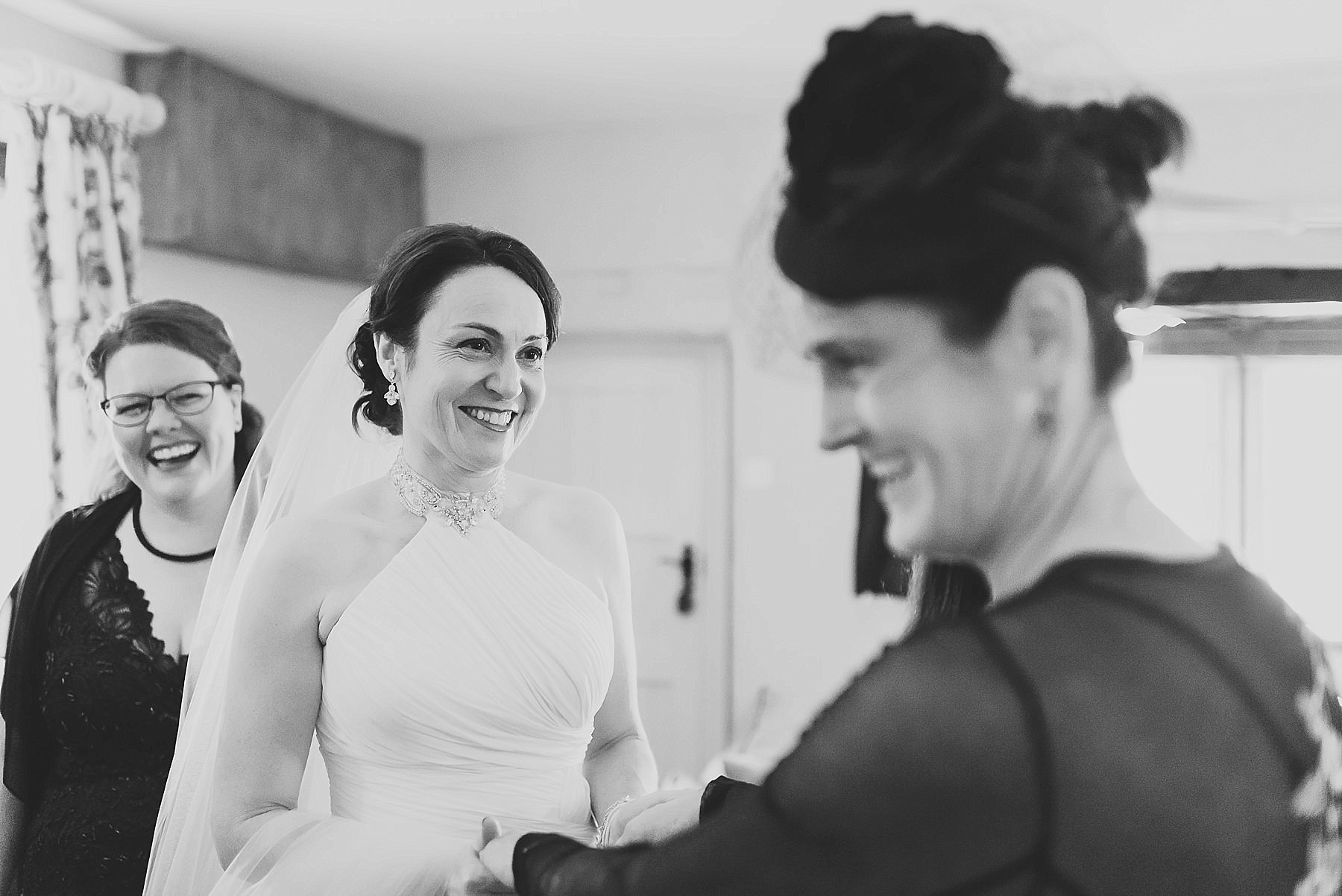 bride in her wedding dress laughing with her friends