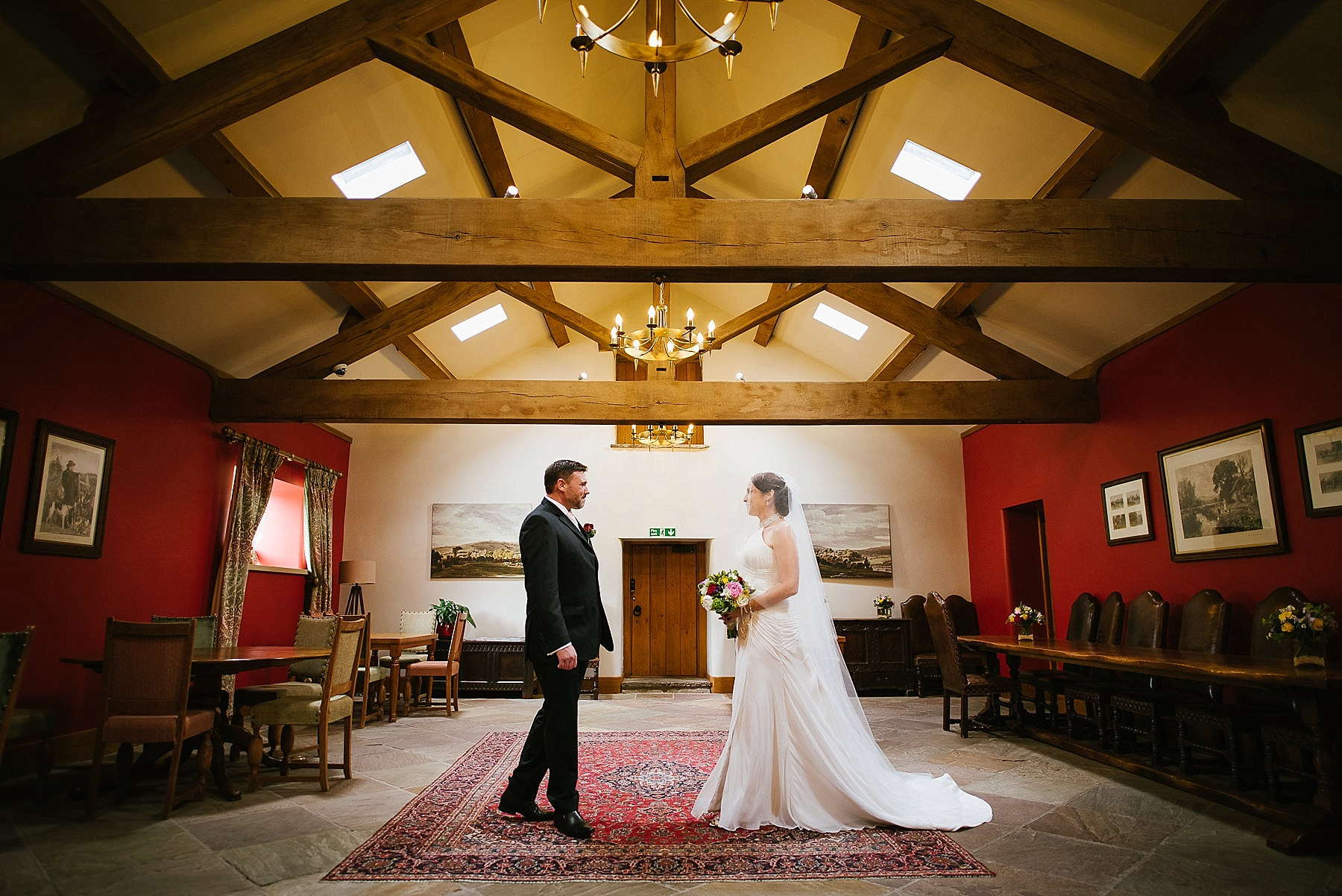 The bride and groom walk towards each other inside Browsholme Hall