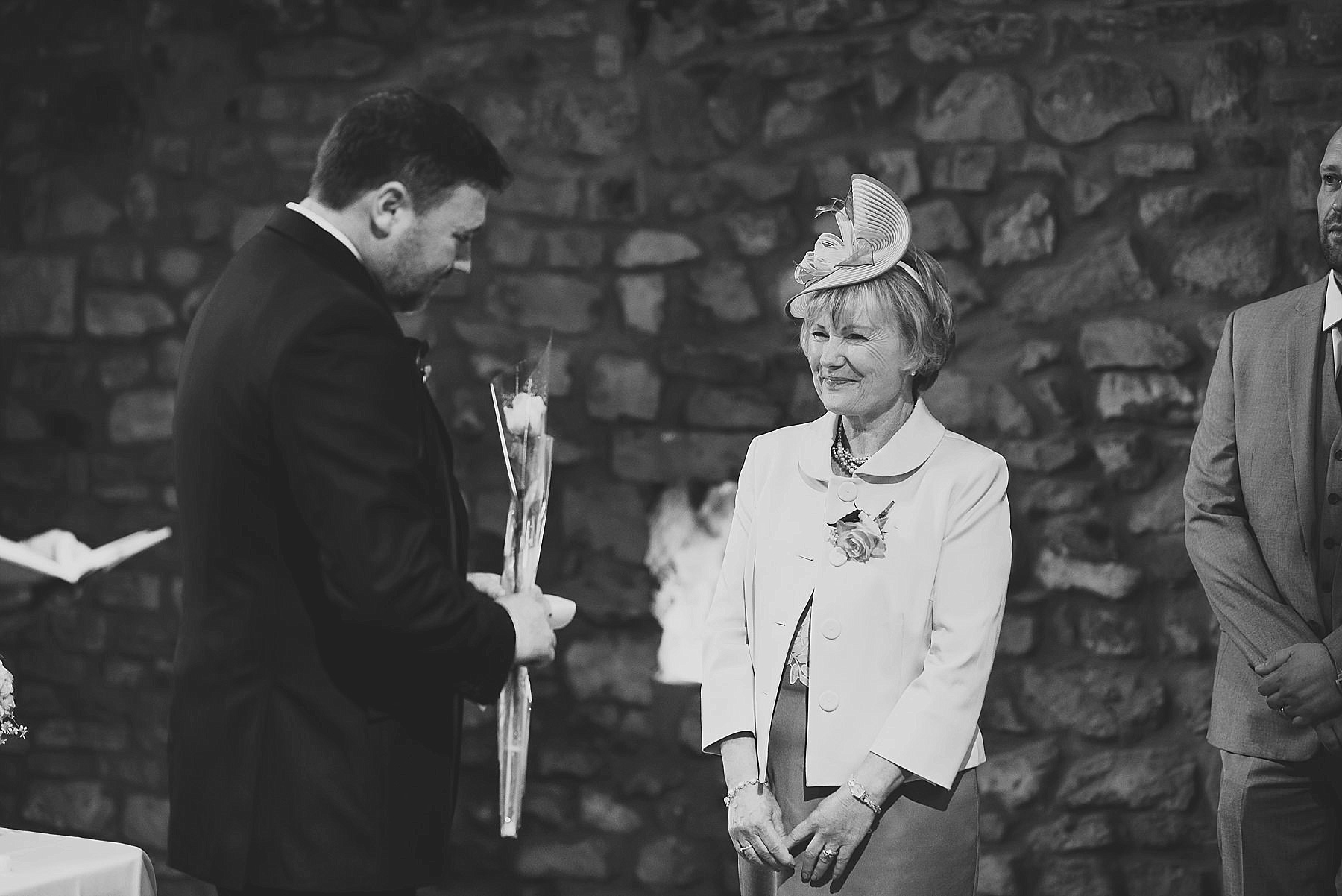 Mum smiling at her son the groom