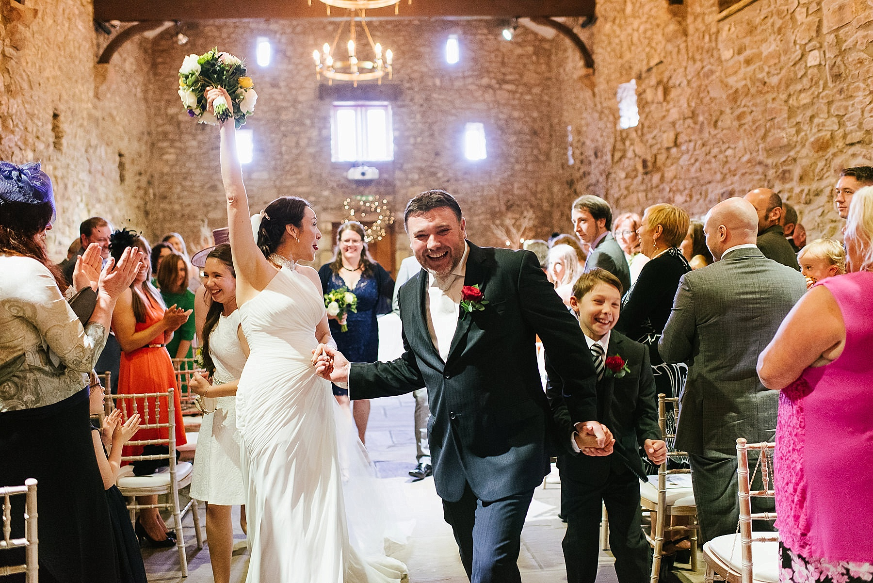 running down the aisle with bouquet in the air