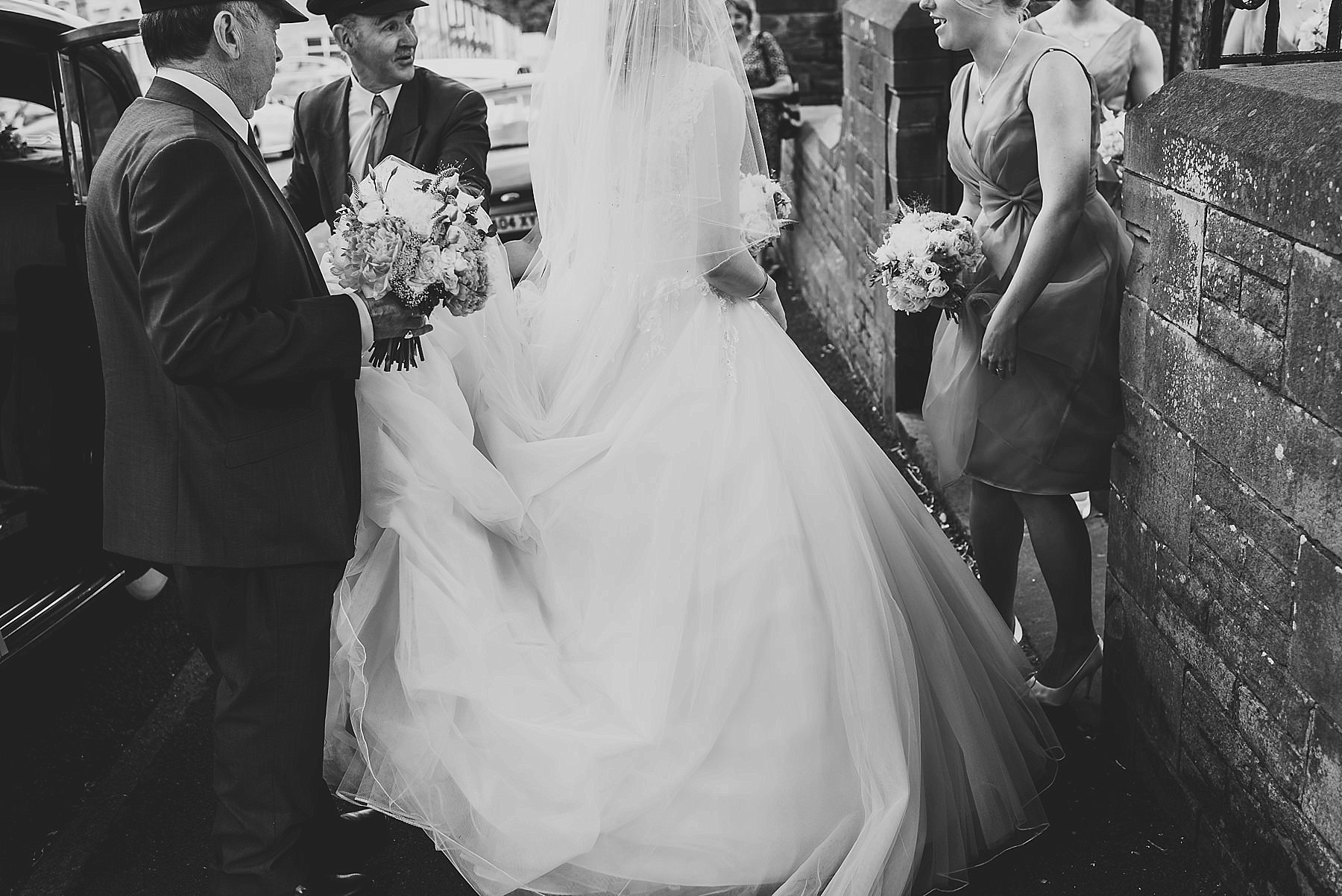 chauffeurs holding wedding dress