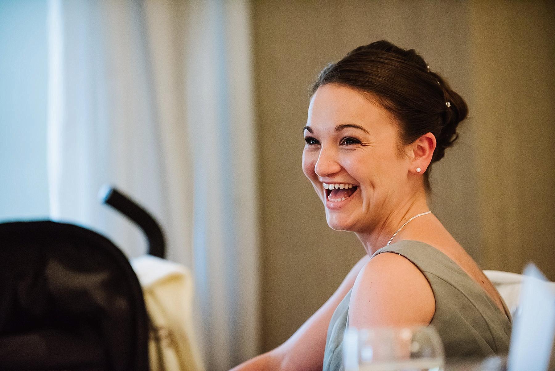 A natural shot of the bridesmaid laughing at the wedding