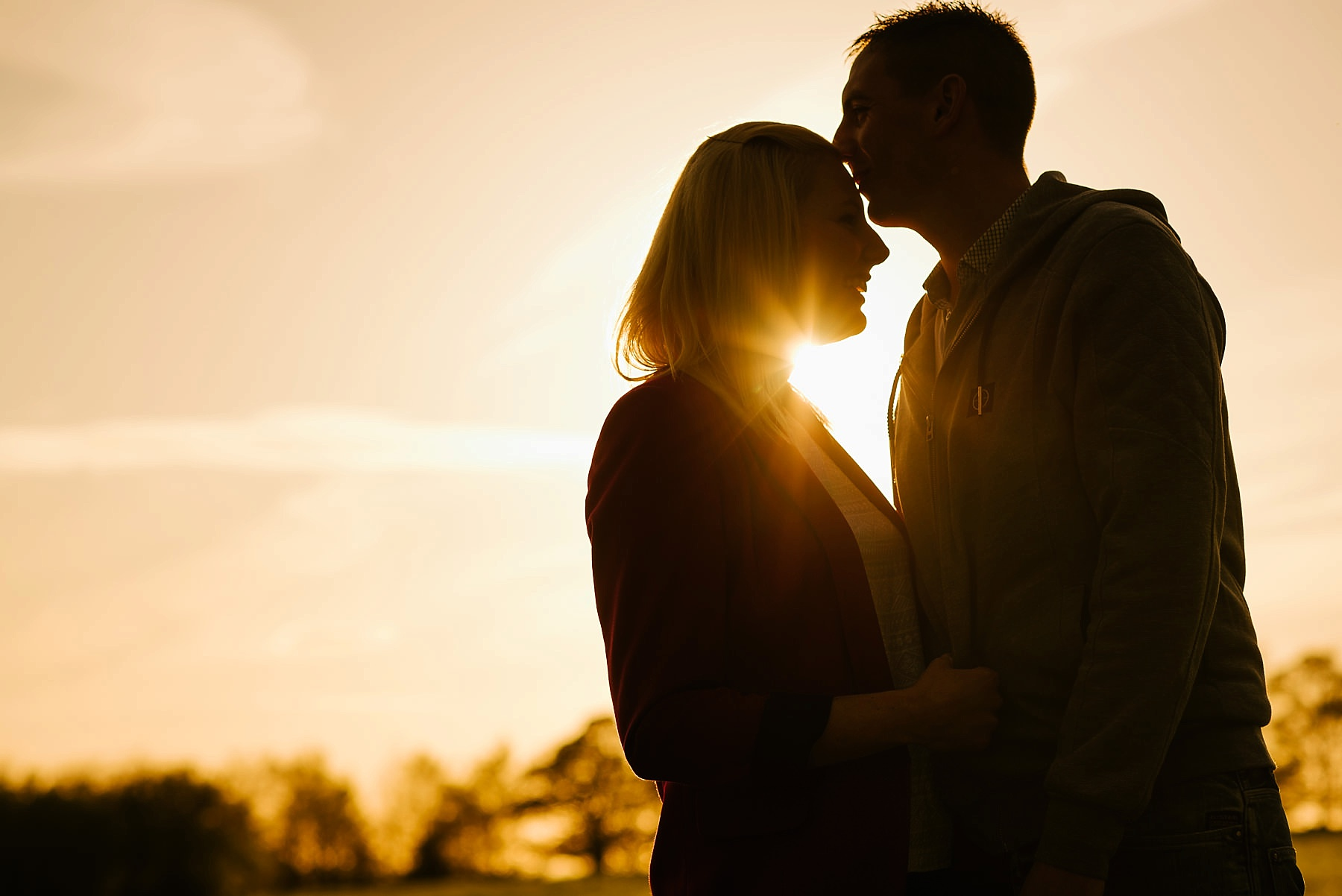 Man kissing woman on head at sunset