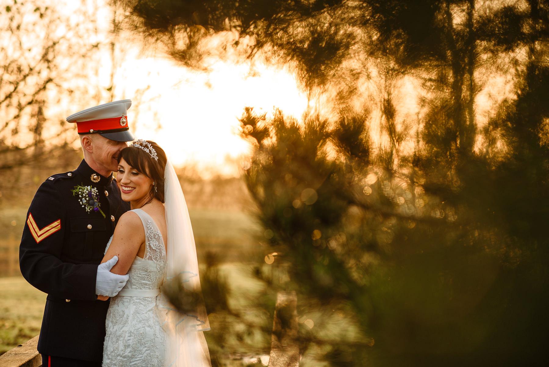 Military groom cuddling his bride at Charnock Farm near Leyland at sunset