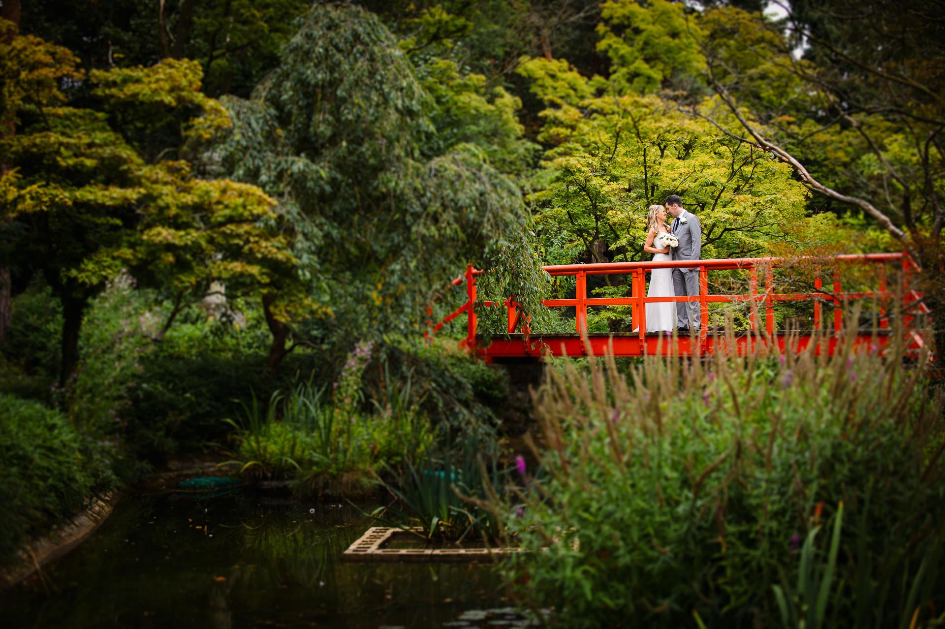 Sarah and Dan on a bridge at the lake of fanhams hall hotel hertfordshire