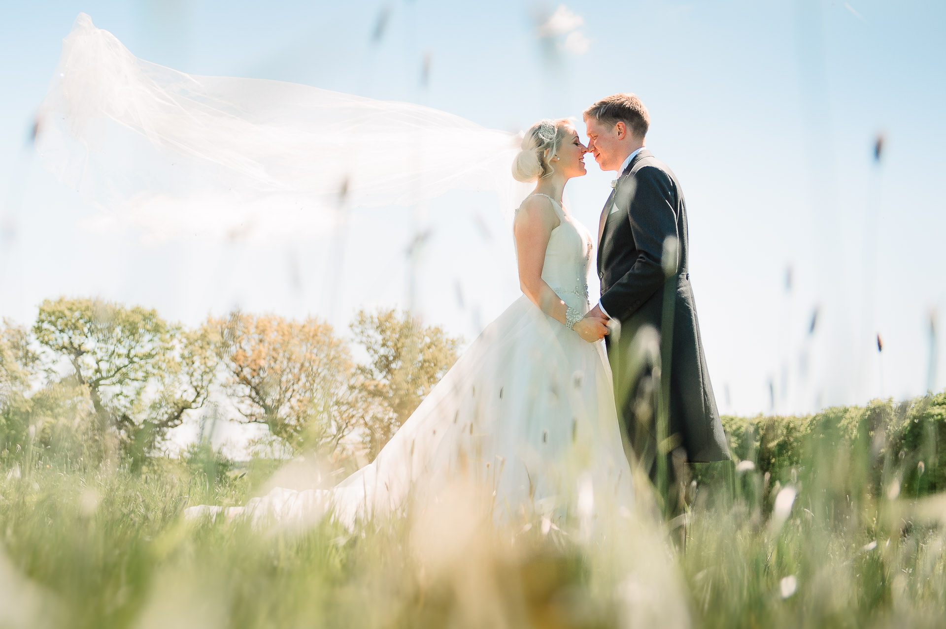 A bride and groom in the fields of Beeston Manor on their wedding day