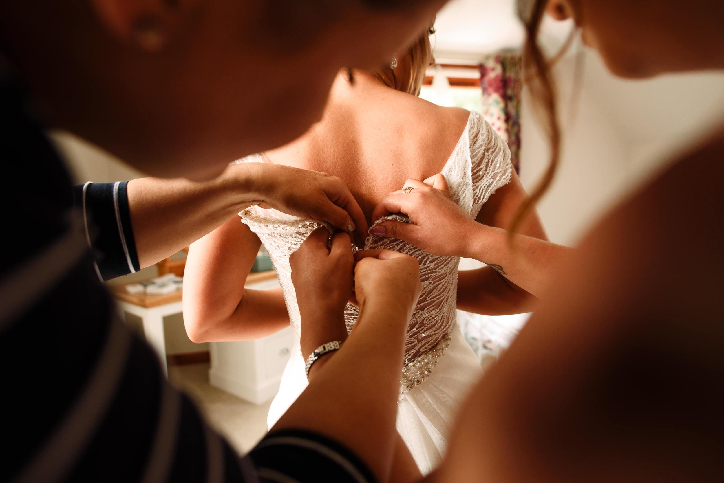 bridesmaids doing up a brides dress
