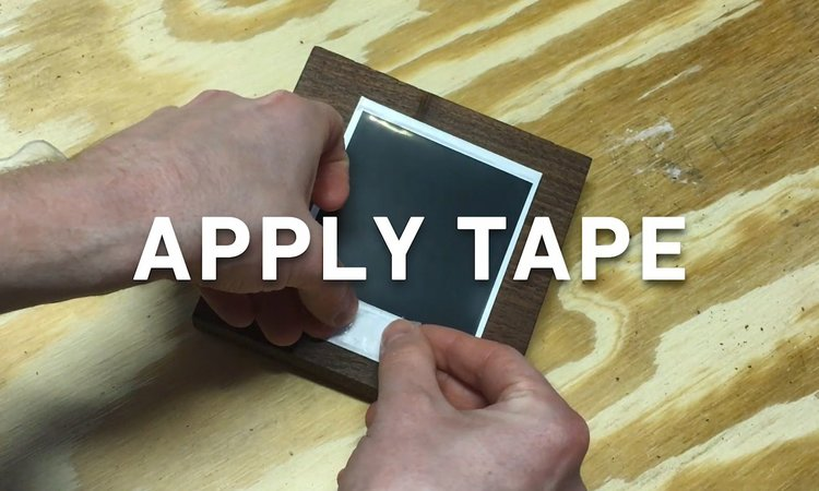 STEP 6 - APPLY THE TAPE || Pull off two strips of double sided tape and apply to the back of the top and bottom of the photo. Flip the photo over, center on the board and press firmly to adhear to the wood.