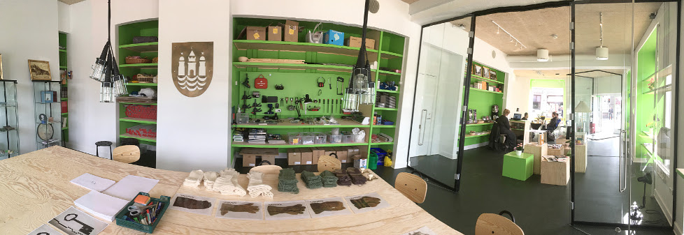 Interior of Storm20 makerspace. Knitted glove reconstructions are on the table in the foreground. The ones with two thumbs are on the far right.