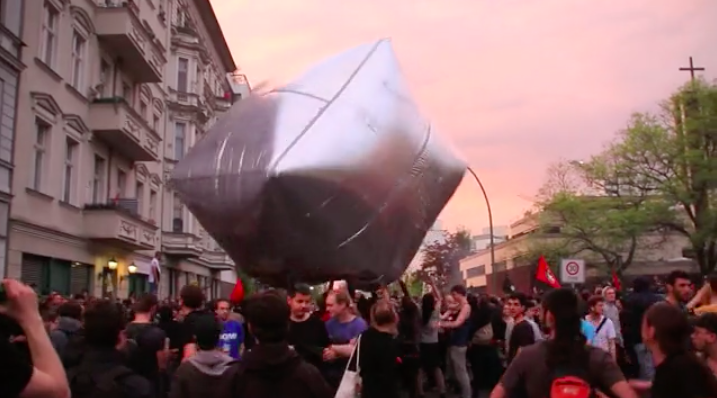 "Screen grab from Inflatable Cobblestones Berlin Part 2 ( Vimeo ), by Artur (presumably Artúr van Balen), 2012  The video is captioned:  On the 25th revolutionary 1st of May demonstration in Berlin-Kreuzberg, protesters were throwing huge inflatable cobblestones, made of silver-reflective foil and tape. The creative intervention was initiated by the art-activist collective ""Eclectic Electric Collective"" (EEC) and was meant as a celebration of an object which is both a symbol and a material weapon of anti-authoritarian struggle everywhere. It also aimed to bring new strategies of tactical frivolity into the demonstration. http://eclectic-electric-collective.blogspot.de/2012/05/under-pavement-beach-gigantic.html"