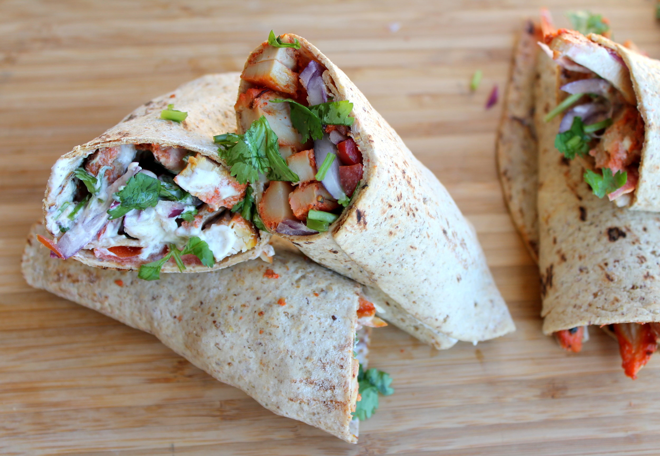 Chicken Tikka Wrap, a quick, healthy, flavorful option for a weeknight dinner or lunch. Juicy chicken tikka pieces are tightly wrapped with delicious spread and toppings. Vegetarian, vegan alternatives available!