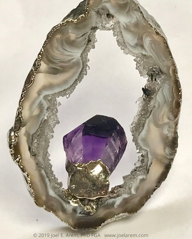 joelarem Another Brazilian agate geode from the 1970s, made into a pendant with a small amethyst crystal and electroformed setting. Sometimes nature makes a picture frame that is about as perfect as it can get. This little gem is about 2 inches tall. #gems#agate#Brazilagate#jewelry#geode#nature#fashion#etsyseller#gemphotography#mineralphotography#beauty