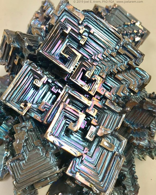 "Bismuth crystals, grown from a melt more than a decade ago. This photo shows a small portion of what may be one of the largest examples of crystallized bismuth in existence, measuring 22x15 cm and weighing about 1.7 kilograms. Bismuth, element #83 in the Periodic Table, is a brittle silvery metal that has been known for centuries and used as a component of low melting point alloys. It was widely employed as such to make metallic type because it expands when it cools, thereby completely filling a mold. Extremely pure bismuth has the amazing ability to form these ""hopper"" crystals, a result of rapid edge-growth. If a pot of melted bismuth is poured just before it completely solidifies, the crystals forming in the melt will instantly develop a thin oxide coating which creates an iridescent tarnish.  #joelarem.com#bismuth#crystalgrowth#crystals#crystalgrowing#nature#crystallography#metaphysical#iridescence#beauty#nature#science#etsyseller#metals"