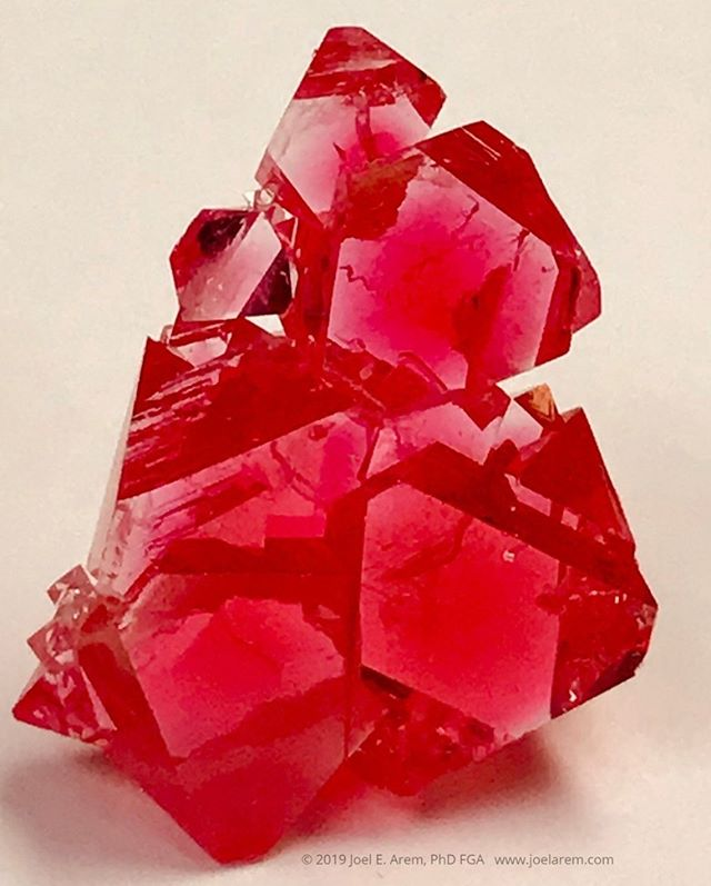 Synthetic flux-grown spinel, magnesium aluminum oxide + chromium, 25 mm tall, grown for research purposes in the early 1970s. Many of the gemstones in use today have synthetic counterparts. Some of them (such as ruby) were first produced more than a century ago. The term homocreate is correctly used with reference to laboratory products that have naturally occurring mineral analogs. Modern factories employ a variety of methods for growing crystals. The ones grown from a flux (molten chemical of some kind) typically show the same morphology as their natural counterparts, vividly true in the case of both garnets and spinel. #www.joelarem.com#crystals#laboratory#synthetics#syntheticgems#fluxgrowth#gemstones#beauty#nature#technology#science#spinel