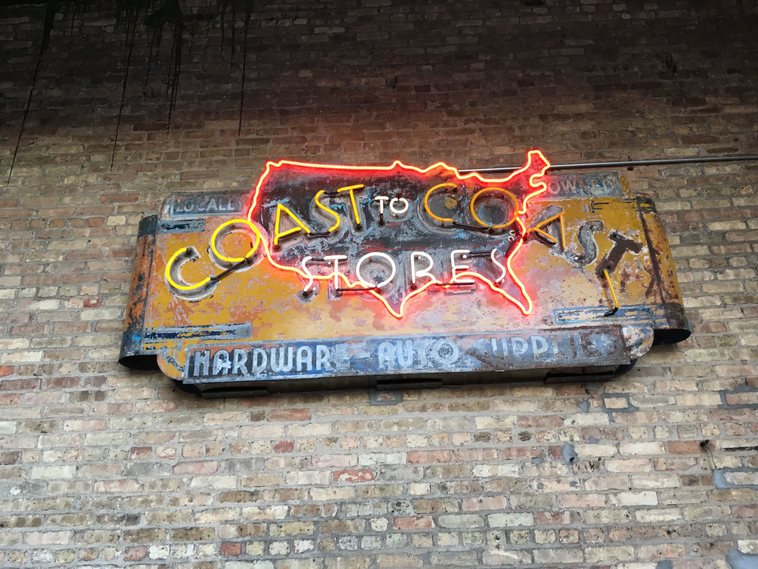 A historic hardware store sign on display outside Lake Monster Brewing.