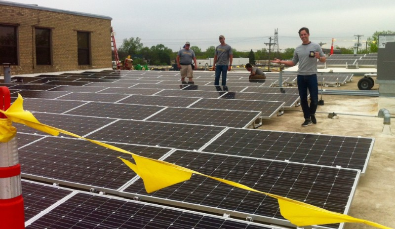 Niles Deneen checks in with the All Energy Solar installers busy on the roof of the pottery on Endicott Street.
