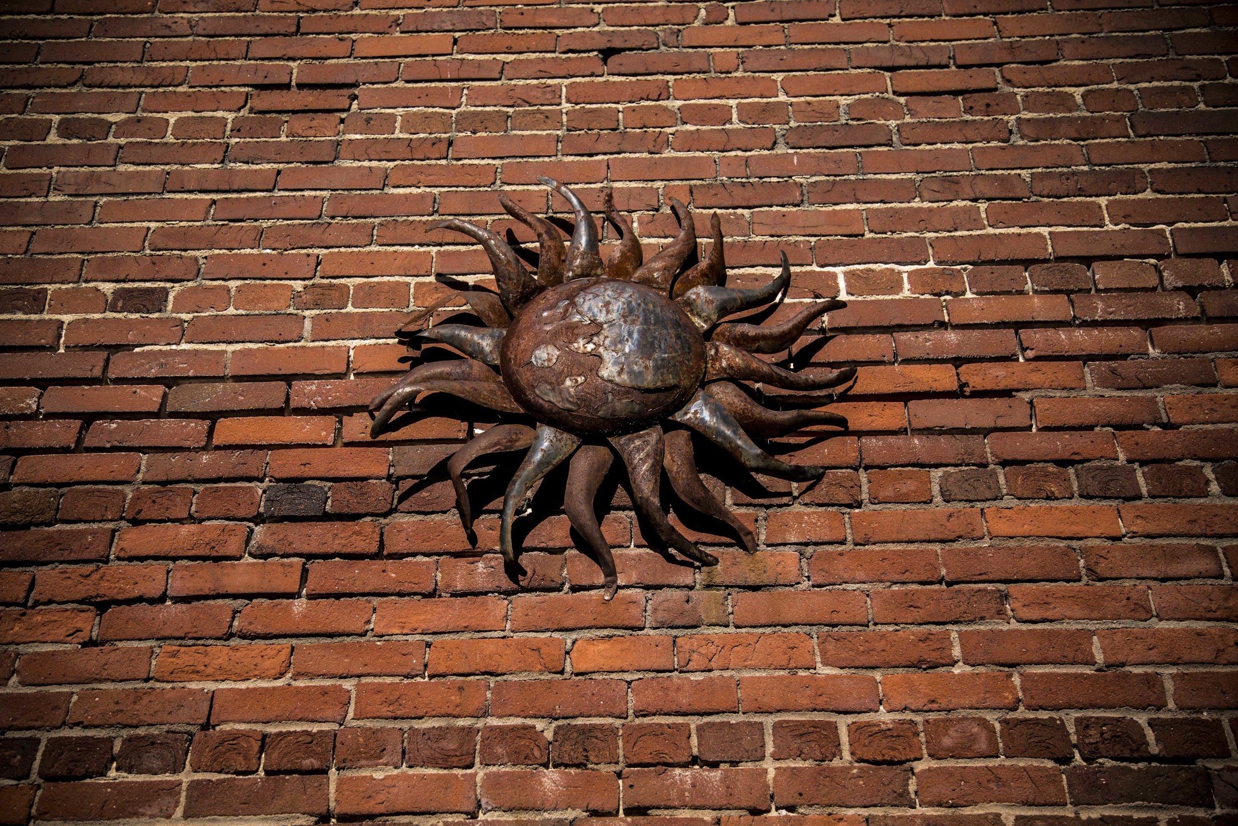 Metal sun sculpture on wall, Pearl Mill Flats, Durham condominiums