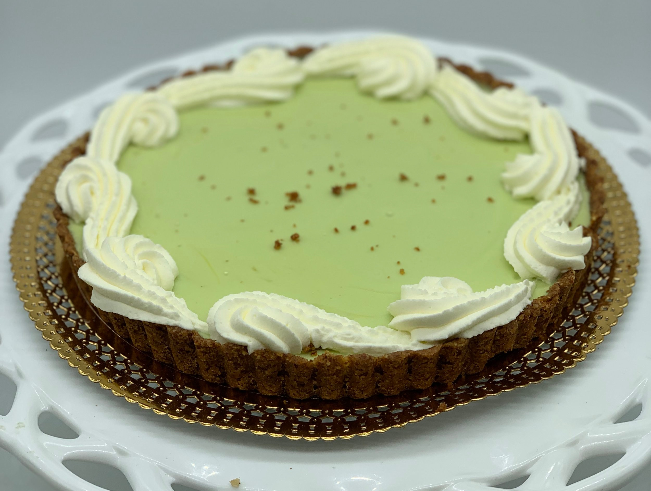 Key Lime Tart - Sweet almond pastry crust filled with a tart key lime filling and finished with whipped cream~Also available in an individual size~