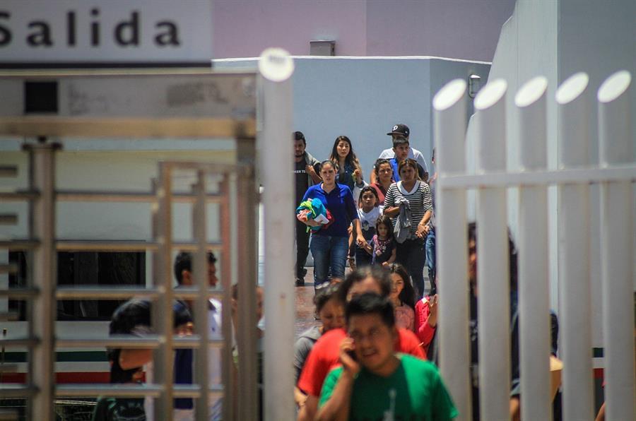 Decenas de migrantes, la mayoría con niños, retornan a territorio mexicano por la garita del chaparral, en la ciudad de Tijuana, del estado de Baja California.jpg