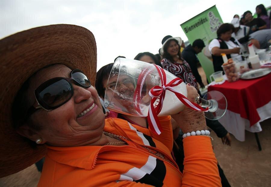 Una mujer prueba un trago de pisco en Perú.jpg