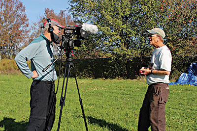 """Huey Coleman filming John Bunker collecting wild apples, for Coleman's next documentary, """"Henry David Thoreau: Surveyor of the Soul."""" photo by Judy Wentzell"""