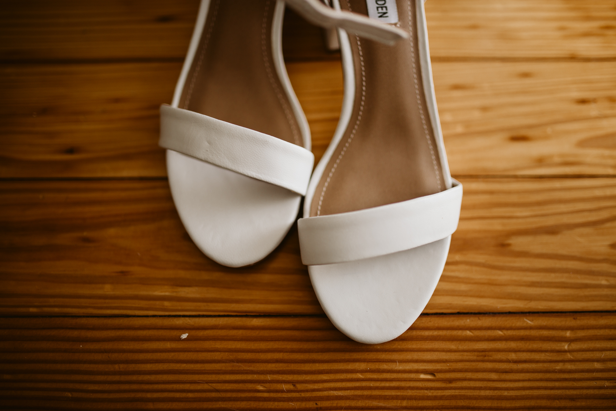 Bride's wedding shoes on the wooden floors of stone house of st charles