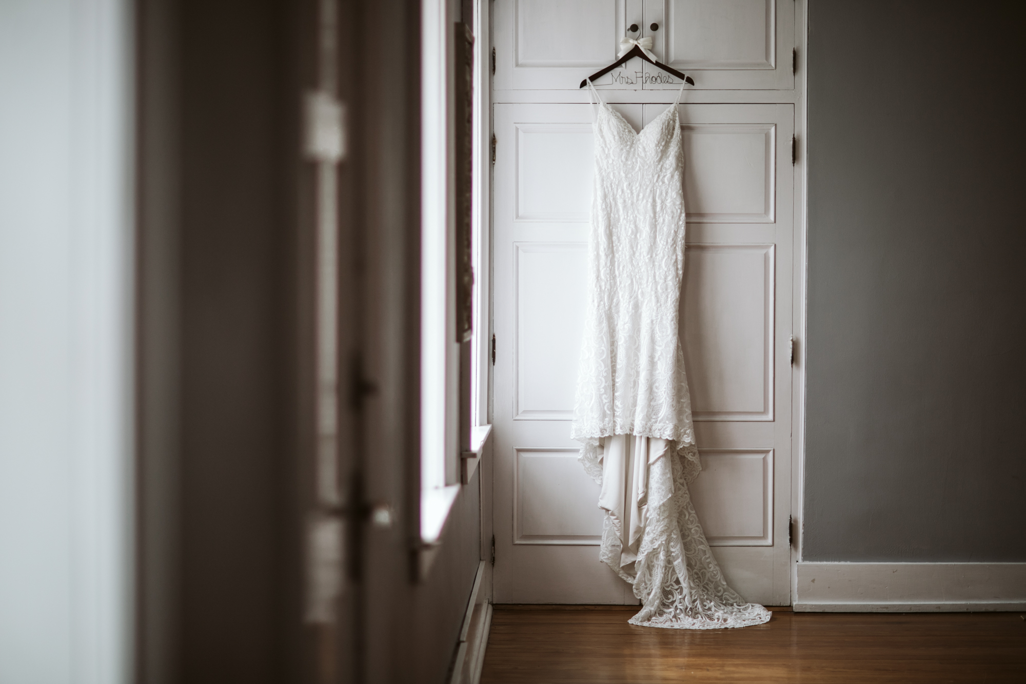 Wedding dress hung beside a window in the Stone House of St Charles