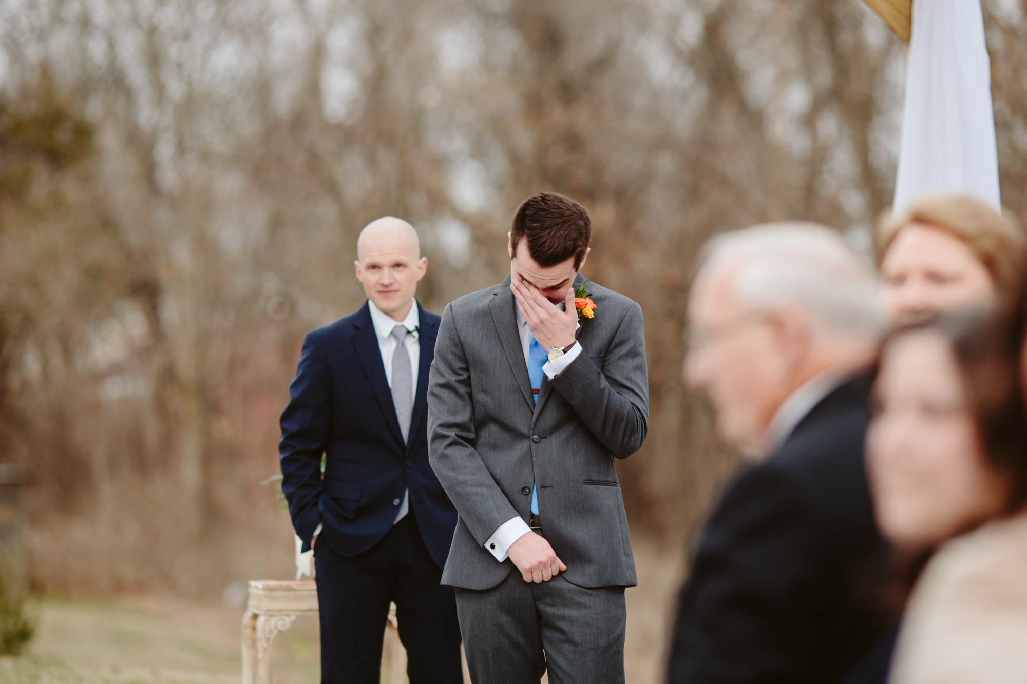 Groom seeing his bride for the first time down the aisle outside at the stone house of st charles wedding venue