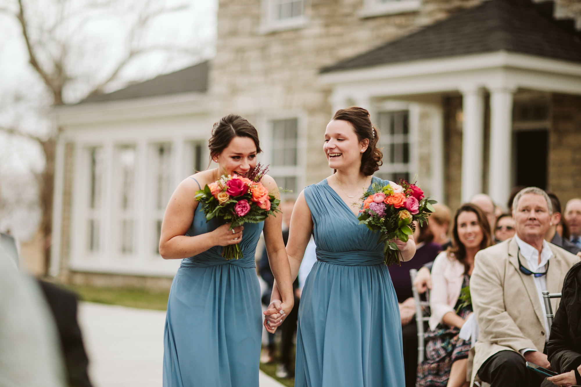 Bridesmaids, the bride's sisters, tearing up as they walk down the aisle at the stone house of st charles
