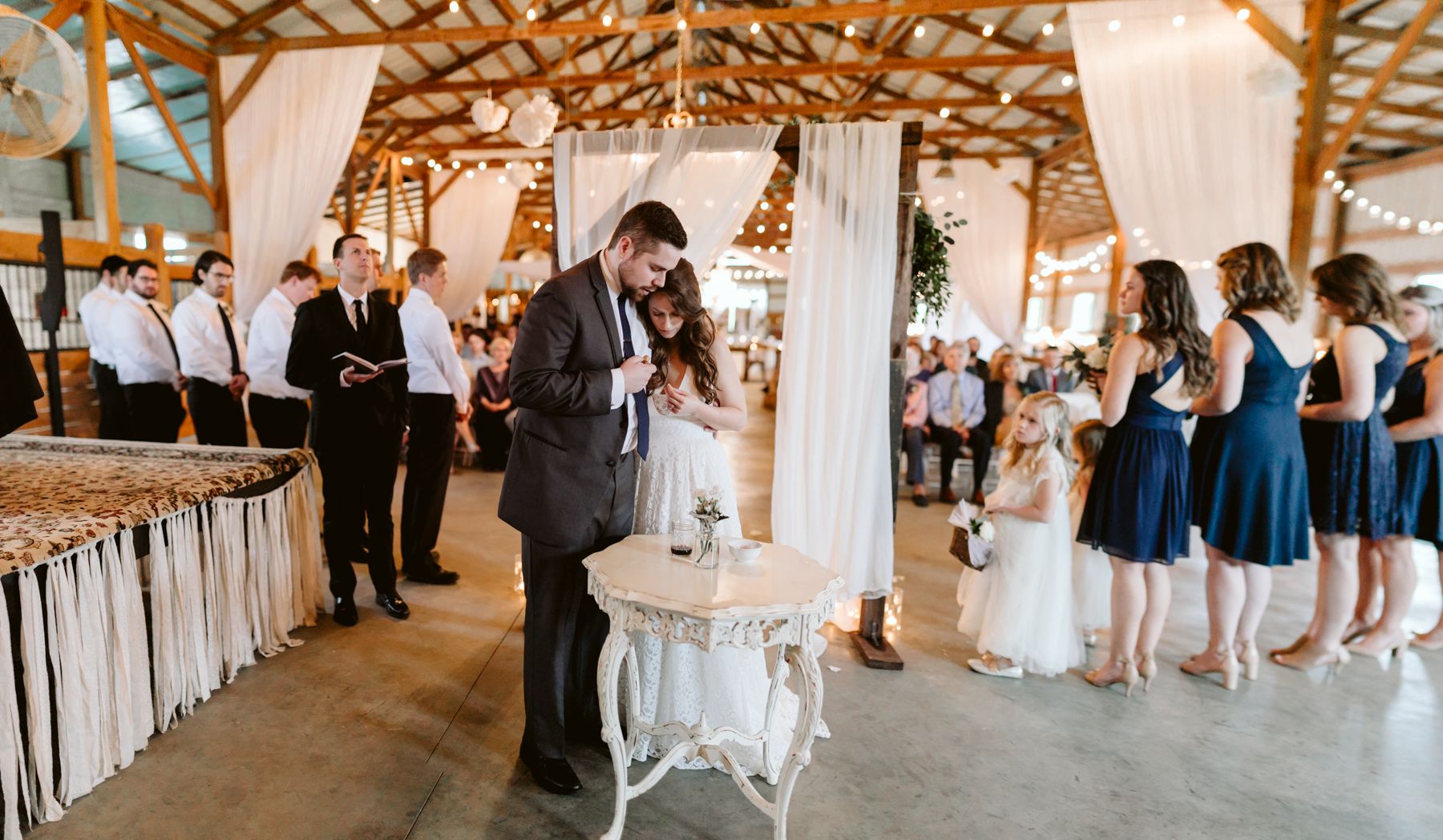 Bride and groom take communion during their ceremony at A Rustic Wedding at Barn in the Bend in Nashville, Tennessee