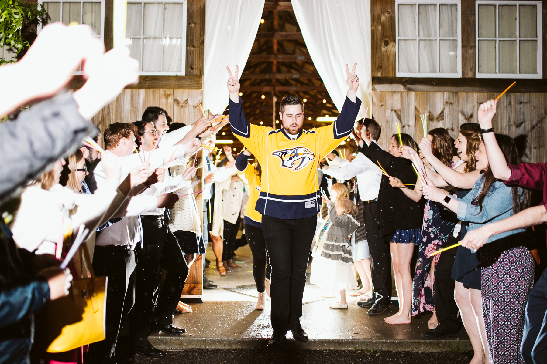 A Nashville predators themed Glow stick exit after a rustic wedding at Barn in the Bend in Nashville, Tennessee