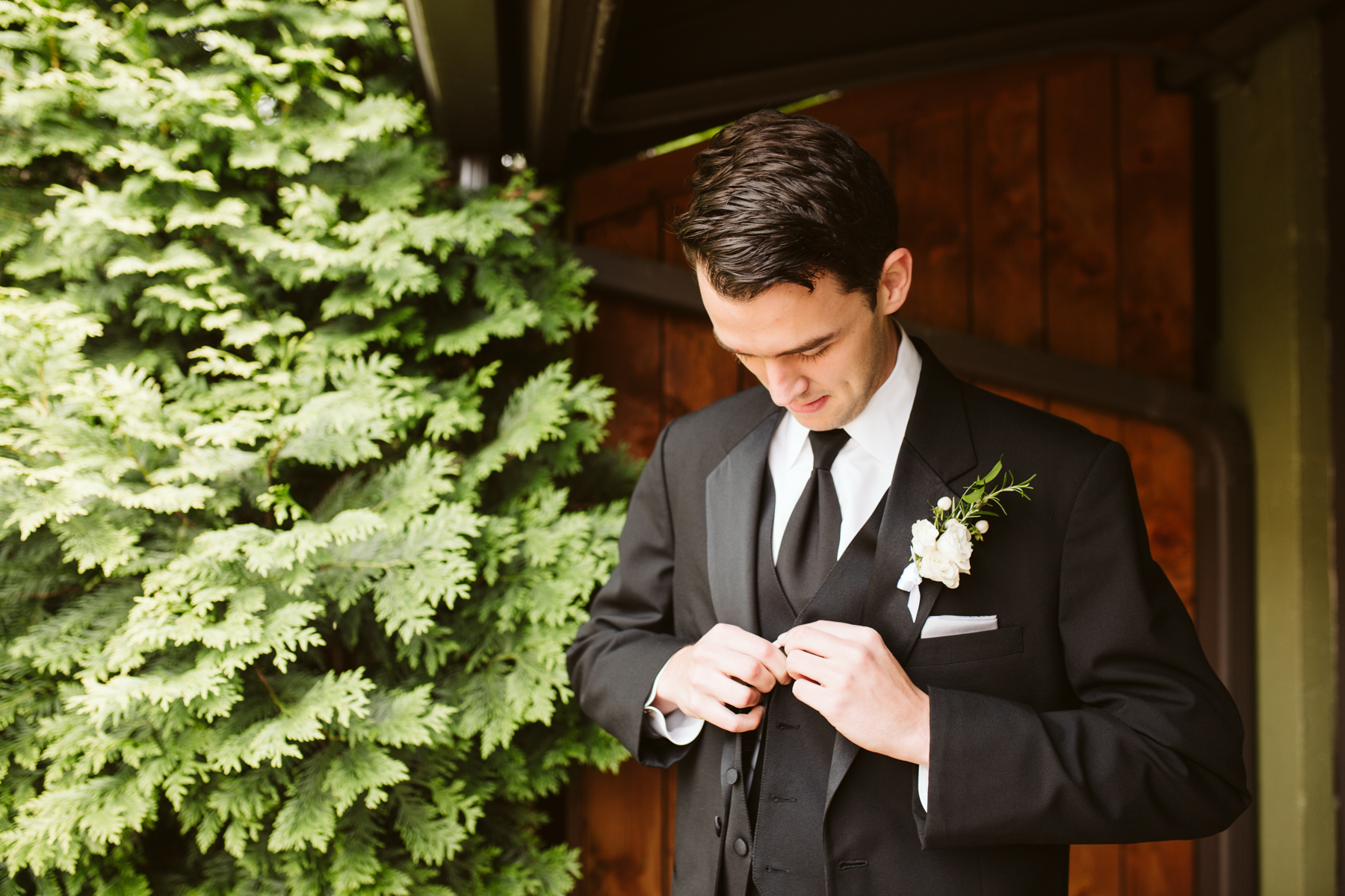 groom buttoning his jacket before a rainy summer wedding at brentwood hills church in Nashville, tennessee