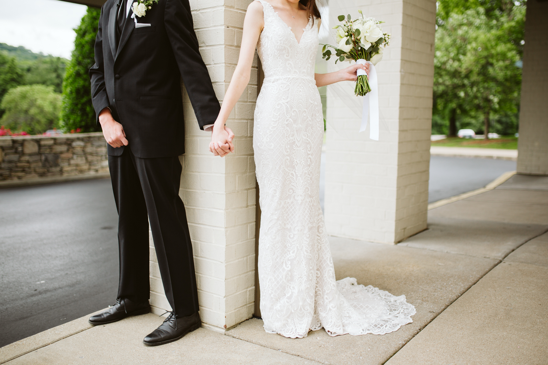 bride and groom pray around a corner together before their rainy summer wedding at brentwood hills church in Nashville, tennessee