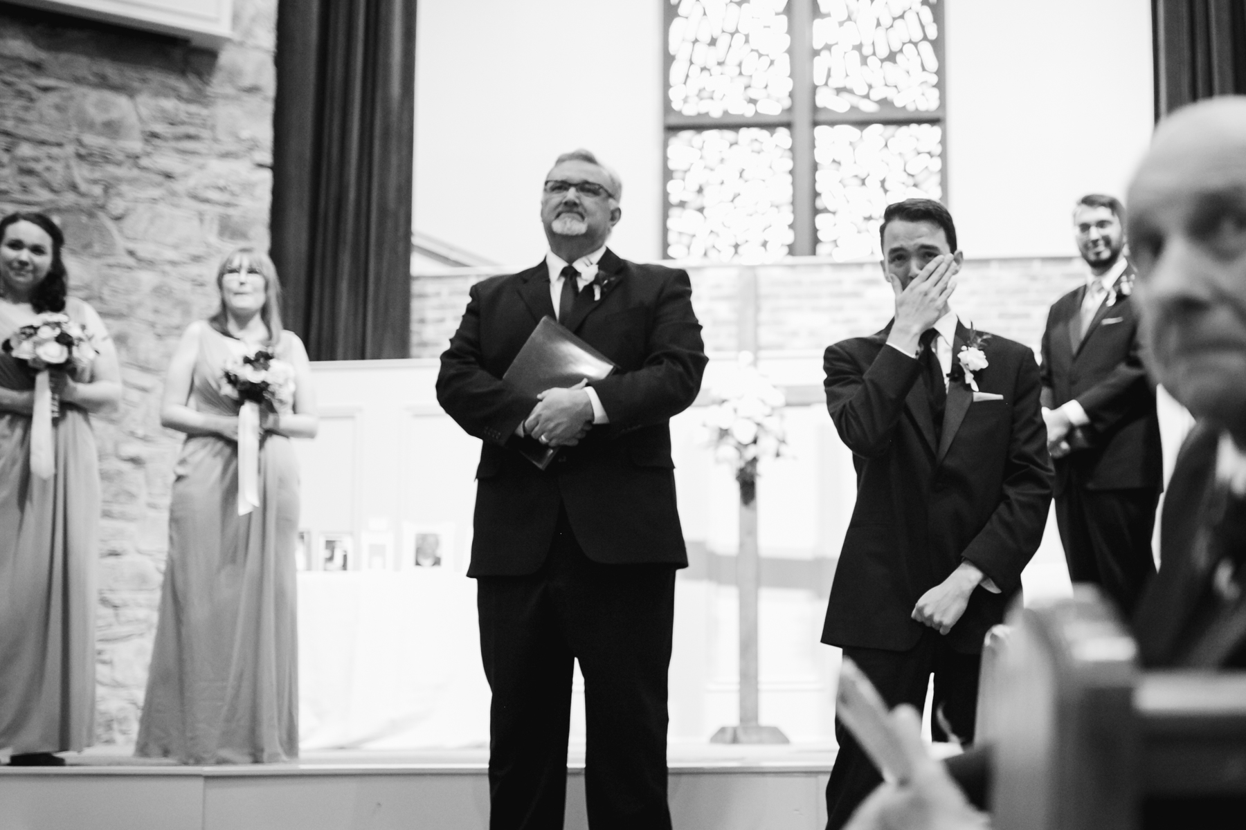 Groom seeing his bride for the first time down the aisle at a rainy summer wedding at brentwood hills church in Nashville, tennessee