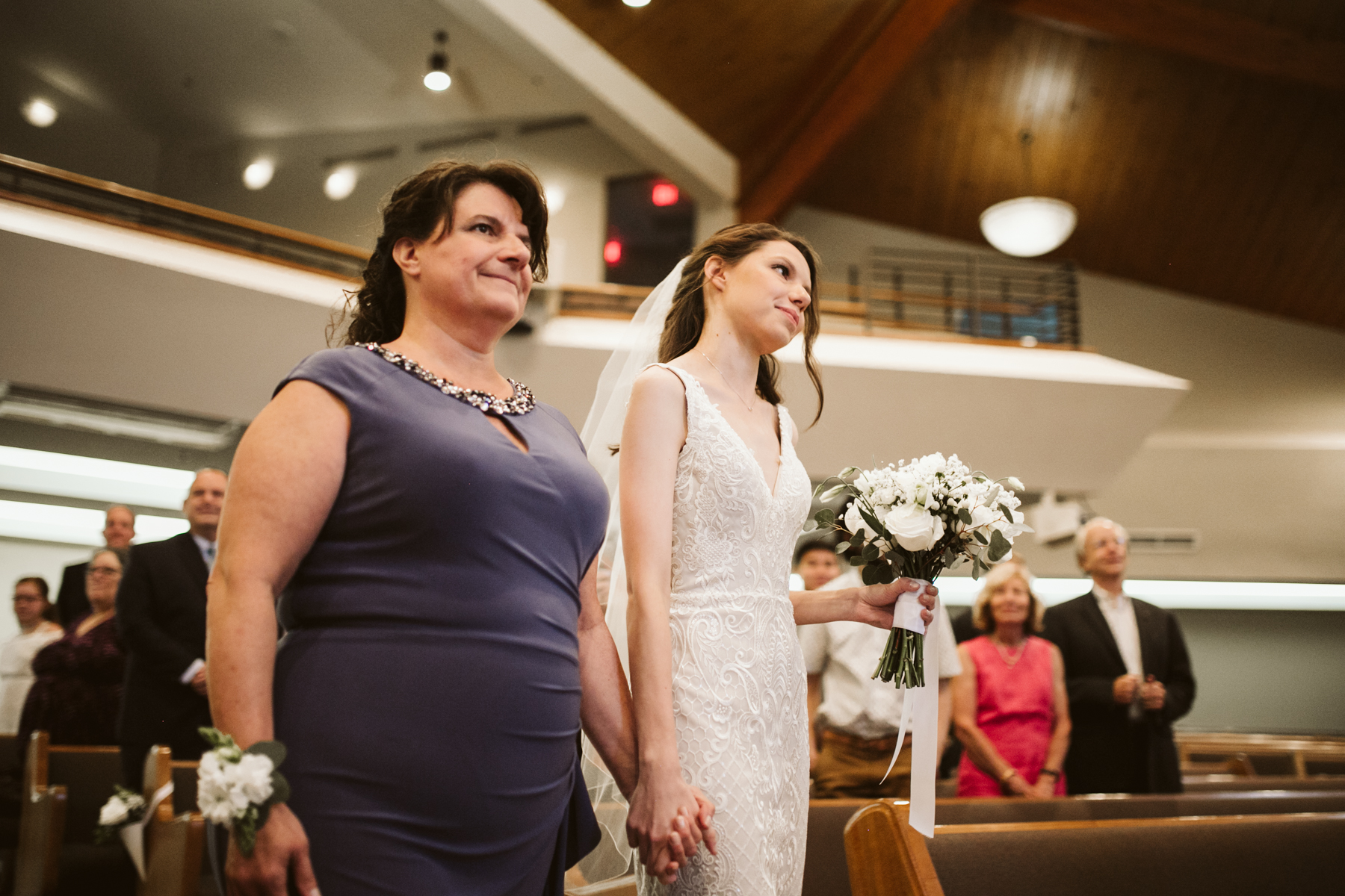 mother and daughter walk down the aisle at a rainy summer wedding at brentwood hills church in Nashville, tennessee