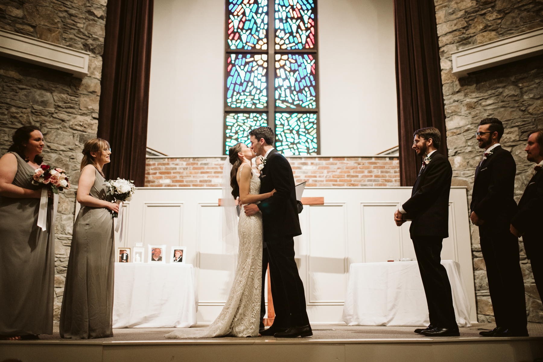 the first kiss during a rainy summer wedding at brentwood hills church in Nashville, tennessee