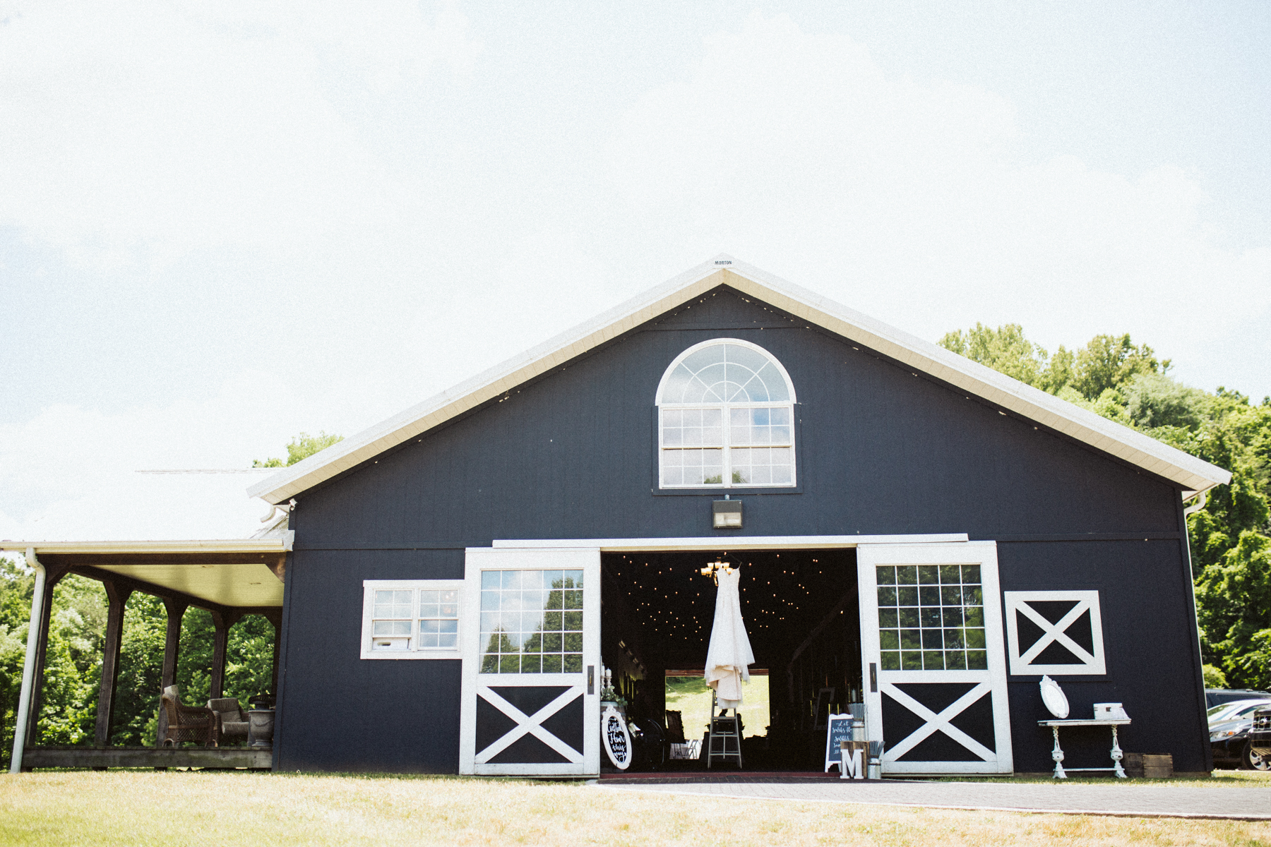 wedding dress hanging in the barn at a stables at strawberry creek wedding in Knoxville, tennessee
