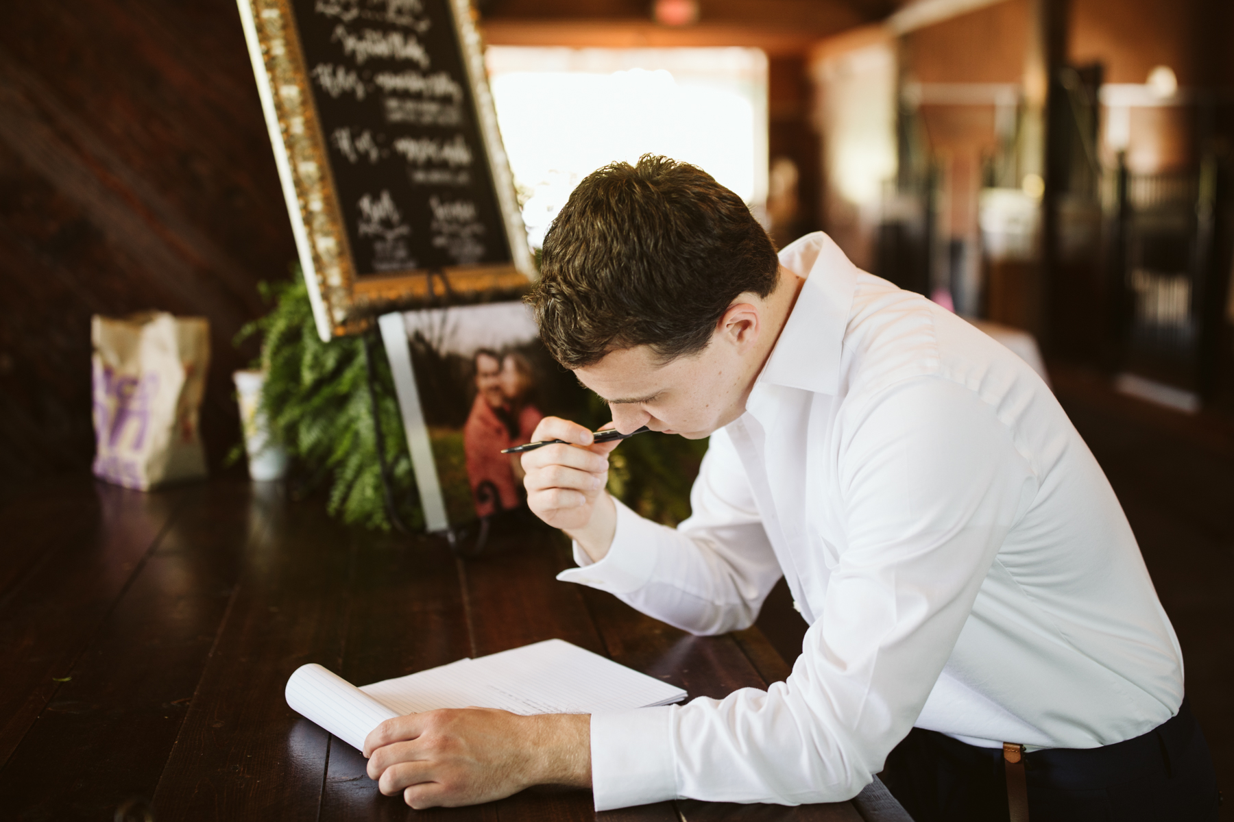 Groom writing out his vows before a stables at strawberry creek wedding in Knoxville, tennessee