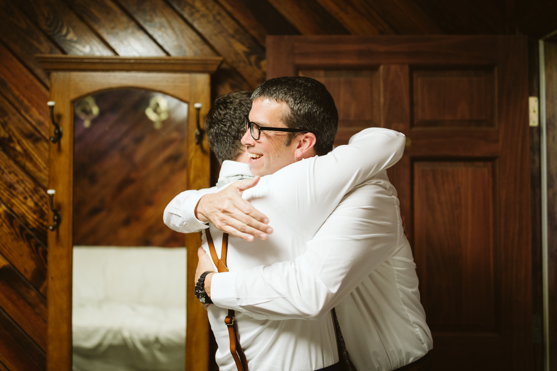 groom and father of the bride hugging before a stables at strawberry creek wedding in Knoxville, tennessee