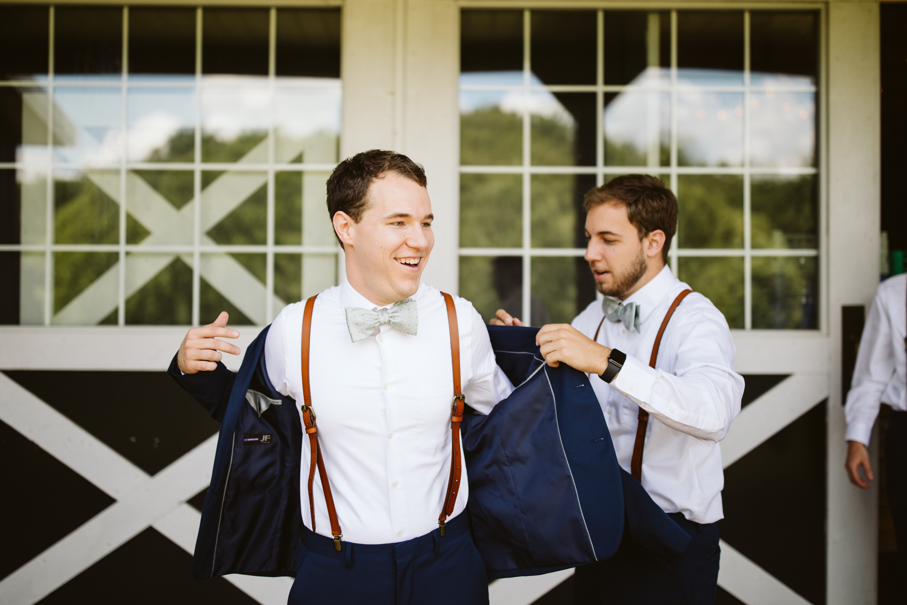 Groom putting on his jacket before a stables at strawberry creek wedding in Knoxville, tennessee