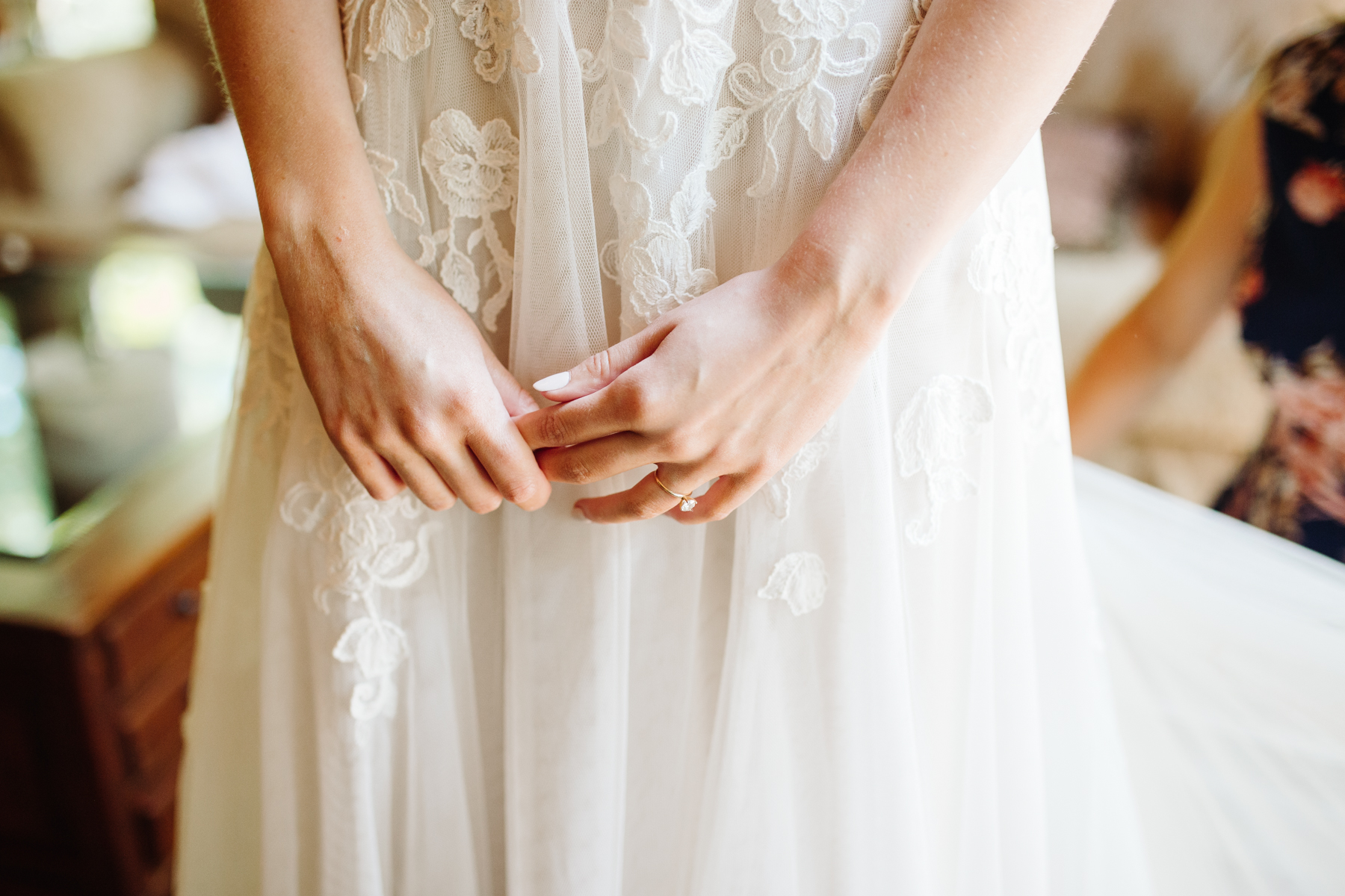 A bride waits as her mom zips up her dress before her stables at strawberry creek wedding in Knoxville, tennessee